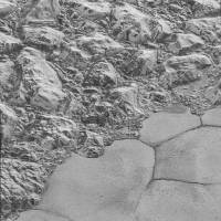 A mountain range on the edge of Pluto's Sputnik Planitia ice plain — with dune formations clearly visible in the bottom half of the picture — is shown in this handout image taken during the July 2015 New Horizons mission. | NASA/JOHNS HOPKINS UNIVERSITY APPLIED PHYSICS LABORATORY / SOUTHWEST RESEARCH INSTITUTE / HANDOUT / VIA REUTERS