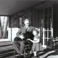 Polio victim President Franklin D. Roosevelt, photographed by his friend Margaret 'Daisy' Suckley at Top Cottage in Hyde Park, New York, with Ruthie Bie, the daughter of the property caretakers, and his dog Fala in February 1941. | FDR PRESIDENTIAL LIBRARY & MUSEUM / CC BY 2.0