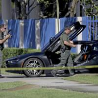 Investigators surround a vehicle after rapper XXXTentacion was shot dead on Monday in Deerfield Beach, Florida. The Broward Sheriff's Office says the 20-year-old rising star was pronounced dead Monday evening at a Fort Lauderdale-area hospital. | JOHN MCCALL / SOUTH FLORIDA SUN-SENTINEL / VIA AP