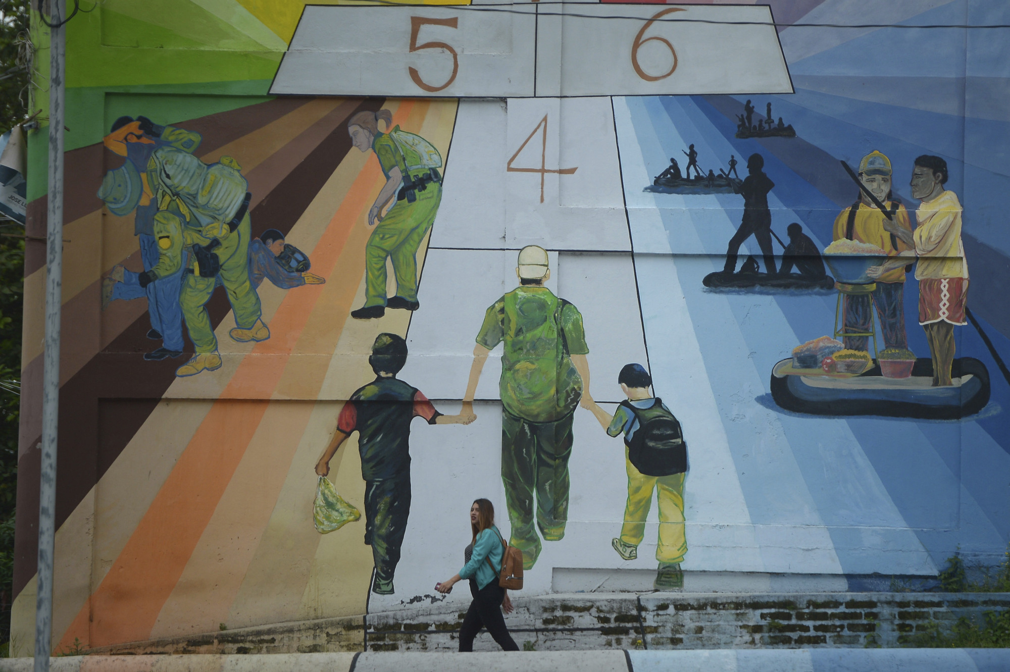 A woman walks past a mural titled 'Migration is not a game of hop scotch,' painted by Salvadorian artist Rafael Moreira, on a residential building at the Monserrat neighborhood in San Salvador Thursday. For now the media ruckus and international outrage caused by the policy of separating children from their parents when they are detained illegally crossing the U.S. border is likely to deter more Central Americans from leaving home, said Andrew Selee, president of the Washington-based Migration Policy Institute. | AP