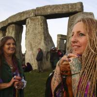 Revellers celebrate the summer solstice at Stonehenge in Wiltshire, England, on June 21, 2018. Modern druids and others gather at the ancient landmark every year to see the sun rise.   AFP-JIJI