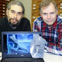 A handout photo released Thursday by the Centre of Excellence in Palaeosciences of the University of the Witwatersrand shows Rob Gess (left) of Rhodes Universtity and Swedish palaeontologis Per Ahlberg posing with the cleithrum of Tutusius and an image of a Devonian tetrapod. The discovery of two Devonian tetrapods in South Africa suggests that the evolution of these creatures from water to land could have occurred anywhere else, and not only in the tropics as was previously thought. | STEVEN LANG / UNIVERSITY OF THE WITWATERSRAND / VIA AFP-JIJI