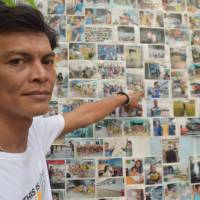 Chairat Ratchapaksi, who founded the Thai and Migrant Fishers Union Group to help trafficked fishermen like him, poses in front of pictures of rescued trafficking victims in Samut Sakhon, Thailand, on March 25. | THOMSON REUTERS FOUNDATION / BEH LIH YI