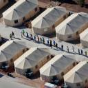 """Immigrant children housed in a tent encampment under the """"zero tolerance"""" policy by the Trump administration walk in single file at the facility in Tornillo, Texas, in the desert near the Mexican border."""
