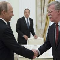 Russian President Vladimir Putin, left, and U.S. National security adviser John Bolton greet each other as Russian Foreign Minister Sergey Lavrov, center, looks on during a meeting at the Kremlin in Moscow, Russia, on June 27. The White House and the Kremlin announced Thursday that leaders of the two countries would meet in Helsinki on July 16. | AP