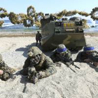 U.S. and South Korean Marines take positions after landing on a beach during the joint Key Resolve and Foal Eagle military exercises in Pohang, South Korea, on March 12, 2016. | YONHAP / VIA AP