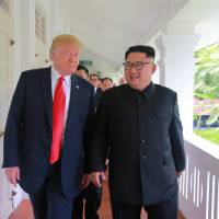U.S. President Donald Trump walks with North Korean leader Kim Jong Un at the Capella Hotel on Sentosa island in Singapore in this picture released on Tuesday by North Korea's Korean Central News Agency. | KCNA / VIA REUTERS