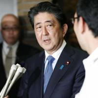 Prime Minister Shinzo Abe talks to reporters on Tuesday night after his conversation with U.S. President Donald Trump. | KYODO