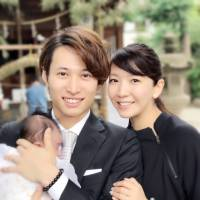 Actress Jun Sena and her husband, Shinji Senda, pose with the baby they adopted, during a visit to a shrine in 2017. | COURTESY OF TOHO ENTERTAINMENT / VIA KYODO