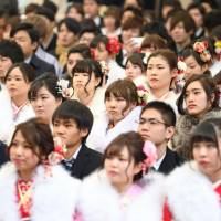 People who turned or were turning 20 attend a Coming-of-Age Day celebration ceremony at Tokyo Disneyland in Urayasu, Chiba Prefecture, on Jan. 8. The Diet on Wednesday enacted a law to lower the age of adulthood to 18 from 20. | KYODO