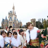Women in kimono take selfies at Tokyo Disneyland in Urayasu, Chiba Prefecture, on Jan. 8 after attending the Coming-of-Age Day ceremony held in the amusement park. | KYODO