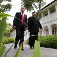 U.S. President Donald Trump and North Korean leader Kim Jong Un walk together after lunch at the Capella Hotel on Sentosa island, Singapore, on Tuesday. | REUTERS