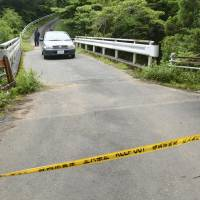 Yellow tape restricts entry to a mountain road Sunday near the site in Fujieda, Shizuoka Prefecture, where a woman's body was found a day earlier. | KYODO