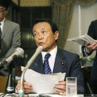 Deputy Prime Minister Taro Aso speaks during a news conference at the Diet building in Tokyo earlier this month. | KYODO
