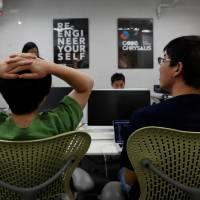 Students attend Code Chrysalis, a software-coding boot camp, at a basement room in Tokyo, on May 23.   REUTERS