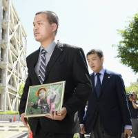 Le Anh Hao (left), father of murdered 9-year-old Vietnamese girl Le Thi Nhat Linh, arrives at the Chiba District Court on June 4 to attend the trial of suspect Yasumasa Shibuya. Prosecutors on Monday demanded the death penalty for Shibuya. | KYODO