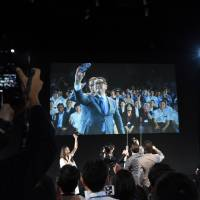 Akio Toyoda, president of Toyota Motor Corp., takes a selfie at an event for 'connected cars' Tuesday in Tokyo. | SATOKO KAWASAKI