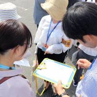 A drill to practice searching for a missing dementia patient is conducted in Takatsuki, Osaka Prefecture, in September. | KYODO