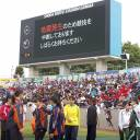 High school students participating in a track and field competition in Maebashi, Gunma Prefecture, on Sunday afternoon look at a board saying that the event has been temporarily suspended following an earthquake.