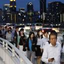 People who gave up waiting for taxis in Osaka's city center walk across the Shin-Yodogawa Bridge over the Yodo River on Monday evening as they try to reach their homes.
