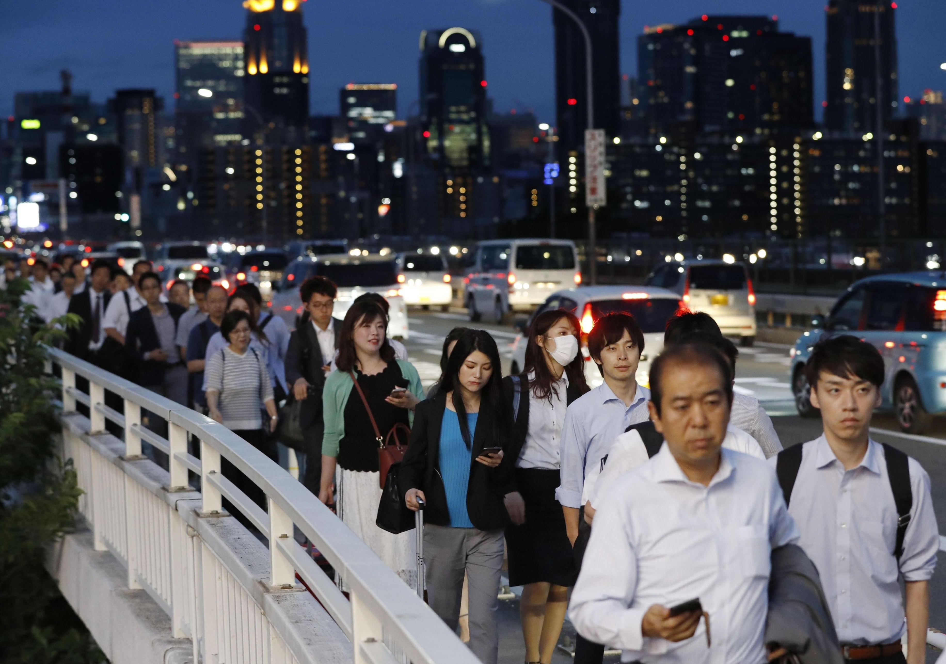People who gave up waiting for taxis in Osaka's city center walk across the Shin-Yodogawa Bridge over the Yodo River on Monday evening as they try to reach their homes. | KYODO