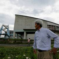 Tour guide Katsuaki Shiga (right) and tourists visit Ukedo Elementary School in Namie, Fukushima Prefecture, on May 17. The school is in an area devastated by the 2011 disaster, near the Fukushima No. 1 nuclear power plant. | REUTERS