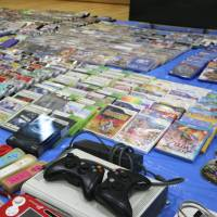 Video game consoles and game titles that police confiscated from bars in Kyoto and Kobe are seen at the Nakagyo Police Station in Kyoto on Wednesday. | KYODO