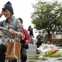 A woman cries near a memorial adorned with flowers for Rina Miyake, 9, who was killed in the major earthquake that hit Osaka Prefecture on Monday morning when a school concrete wall collapsed on her as she was making her way to class. | KYODO
