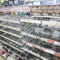 Convenience store shelves are mostly empty on Monday at a convenience store in Ibaraki, Osaka Prefecture, after people flocked to buy food following a strong quake in the area. | KYODO