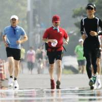Runners jog around the Imperial Palace in Tokyo in the summer heat. | KYODO