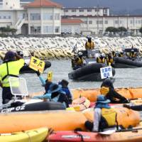 People opposed to the relocation plan for U.S. Marine Corps Air Station Futenma in Ginowan, Okinawa Prefecture, use kayaks and other vessels to protest near the new site being built in Nago's Henoko district on Monday. | KYODO