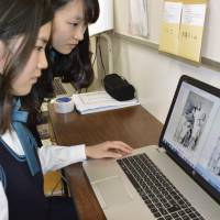 Anju Niwata (left) works on colorizing a black and white photo in the city of Hiroshima in May. | KYODO