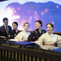 Foreign employees pose at Daiwa Royal Hotel Grande Kyoto, which is set to open Saturday near Kyoto Station. The hotel supports visitors with staff that can speak nine languages. | KYODO