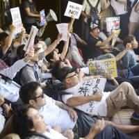 Protesters sit at a public hall in Kawasaki to block people from attending an alleged hate speech event targeting ethnic Korean residents on June 3, two years after Japan's anti-hate speech law took effect. | KYODO