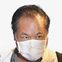 Yoichiro Shinozaki, head of a kimono rental firm that went bankrupt just before Coming-of-Age Day, arrives at Narita airport from the United States on Saturday.   KYODO