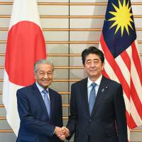 Prime Minister Shinzo Abe, right, and his Malaysian counterpart Mahathir Mohamad shake hands at Abe's official residence in Tokyo on Tuesday. | AFP-JIJI