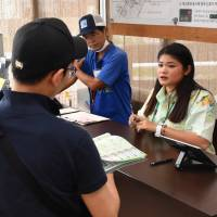 Staff at a Luft Travel Rent-a-Car outlet in Okinawa Prefecture speak to foreign tourists on May 18. | THE OKINAWA TIMES
