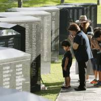 Family members pray for relatives who died in the 1945 Battle of Okinawa at Peace Memorial Park in Itoman, Okinawa Prefecture, on Saturday, the 73rd anniversary of the end of the bloody ground battle. | KYODO