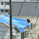 A man covers a damaged roof with a blue plastic sheet in Takatsuki, Osaka Prefecture, on Wednesday after a big earthquake rocked the area last Monday morning.