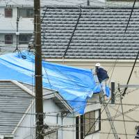 A man covers a damaged roof with a blue plastic sheet in Takatsuki, Osaka Prefecture, on Wednesday after a big earthquake rocked the area last Monday morning. | KYODO