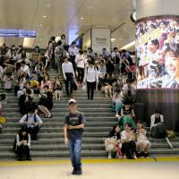 People sit on the stairs of Hankyu Railway's Umeda Station in the city of Osaka on Monday morning, after train operations were suspended following a major earthquake that hit the Kansai region. | KYODO