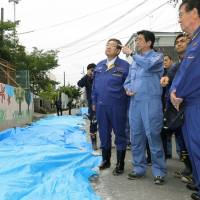 Prime Minister Shinzo Abe inspects a wall of Juei Elementary School in Takatsuki, Osaka Prefecture, on Thursday, which collapsed when a major earthquake hit the area Monday, killing a 9-year-old girl. | POOL / VIA KYODO