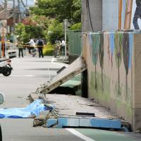 A wall outside Juei Elementary School in Takatsuki, Osaka Prefecture, is seen collapsed Monday following a major earthquake that hit the Kansai region. | KYODO