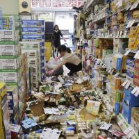 Workers at a liquor store in Hirakata, Osaka Prefecture, clean up scores of cans knocked off the shelves by a strong earthquake that hit the Kansai region Monday. | KYODO