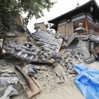 Rubble covers a temple compound in Ibaraki, Osaka Prefecture, Monday afternoon after a powerful earthquake hit northern Osaka Prefecture in the morning. | KYODO