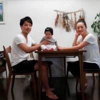 Eri Sato (right) poses with her husband, Tatsuya, and 3-month-old daughter, Sara, at their home in Yokohama on May 23. | REUTERS