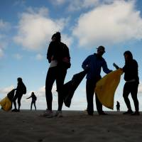 Volunteers pick up plastic during a garbage collection on La Costilla Beach in Rota, Spain, on Saturday. | REUTERS