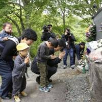 People offer prayers Thursday in front of a cenotaph in Kurihara, Miyagi Prefecture, set up near the former location of the Komanoyu hot spring inn. The inn was engulfed by a landslide triggered by a major earthquake that hit the region 10 years ago. | KYODO