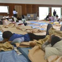 People take shelter at an evacuation center in Takatsuki, Osaka Prefecture, on Tuesday morning after spending a night there. | KYODO