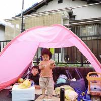 Children evacuate to a tent set up in their garden in Ibaraki, Osaka Prefecture, on Monday.
